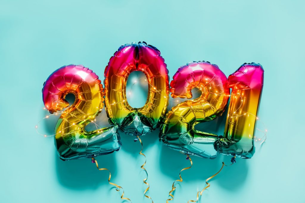 Rainbow colored Foil balloons in the form of numbers 2021 on blue background